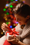 Woman sitting chair and opening Christmas gift Stock Images