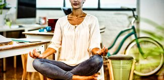 Woman sitting on chair and performing yoga. In office royalty free stock images