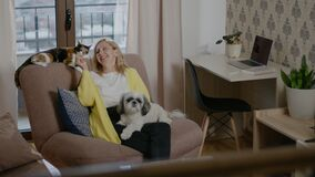 Woman sitting in chair and playing with cat, dog in apartment room rbbro.