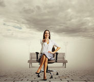 Woman sitting on the chair and pointing. Smiley businesswoman sitting on the office chair and pointing Royalty Free Stock Photo