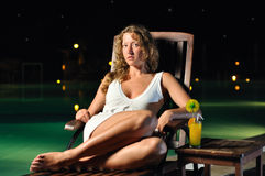 Woman is sitting on chair at poolside at night. Sensual woman is sitting on chair at poolside at night and looking at camera Royalty Free Stock Photos