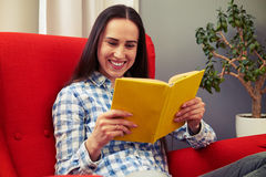Woman sitting on the chair and reading book. Cheerful young woman sitting on the chair and reading book Royalty Free Stock Photography