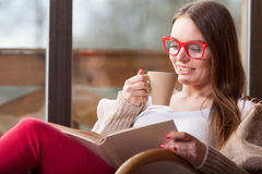 Woman sitting on chair reading book at home Royalty Free Stock Photography