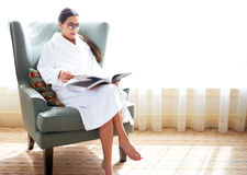Woman sitting in chair reading book. Young woman wearing robe sitting in midcentury modern wingback chair reading book with crossed legs Stock Photos