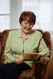 Woman sitting in chair reading. Woman sitting in chair reading electronic book Stock Images