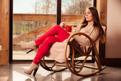 Woman sitting on chair relaxing at home Stock Photography