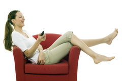 Woman sitting on a chair with remote control Royalty Free Stock Images