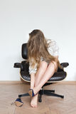 Woman sitting on the chair removing shoes Stock Images