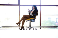 Woman sitting in the chair with smartphone Stock Images