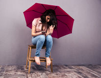 Woman sitting on the chair with smartphone and umbrella Royalty Free Stock Photos