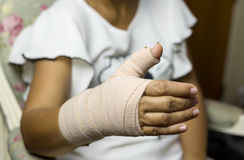 Woman sitting on a chair with Splint broken bone on her hand Royalty Free Stock Photos