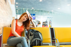 Woman sitting on the chair in a station hall. Royalty Free Stock Photography