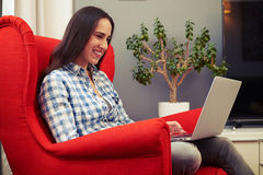 Woman sitting on chair and using laptop at home Stock Images