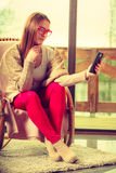 Woman sitting on chair using phone at home Stock Photography