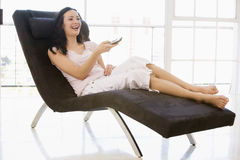 Woman sitting in chair using remote control Stock Photo