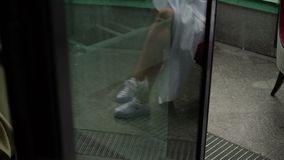 Woman sitting on chair in wedding dress and sneakers stock video footage