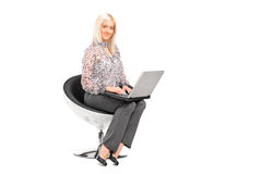 Woman sitting on a chair and working on a laptop Royalty Free Stock Images