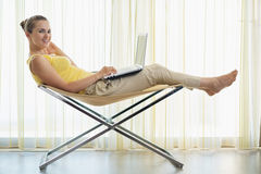 Woman sitting on chair and working on laptop Stock Photography