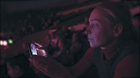 A woman sitting in a circus auditorium takes pictures with a smartphone taking place in the arena. A woman sitting in the auditorium of a circus photographs stock video footage
