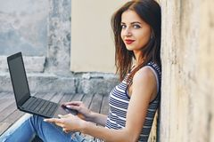 Woman sitting on the city wooden surface and using laptop computer outdoors. Portrait of a happy young woman sitting on the city wooden surface and using laptop Royalty Free Stock Photos