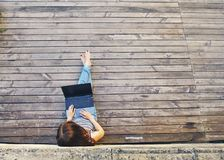 Woman sitting on the city wooden surface and using laptop computer outdoors Royalty Free Stock Photo
