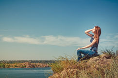 Woman sitting on the cliff Stock Photography