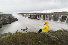 Woman sitting on the cliff edge next to Selfoss waterfall in Vatnayokull national park, Iceland. Woman in yellow raincoat sitting standing on the cliff edge next stock images