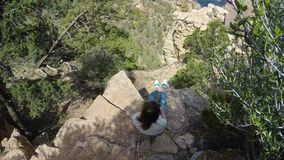 Woman sitting on a cliff. Of Grand Canyon stock video