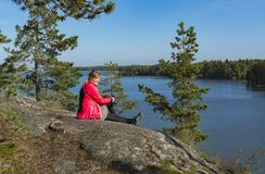 Woman sitting on cliff by the lake. Woman sitting on cliff and watching lake view Stock Image