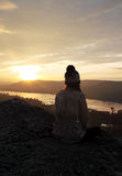 Woman sitting on cliff with sunrise Royalty Free Stock Image