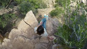 Woman sitting on a cliff. Of Grand Canyon stock video footage
