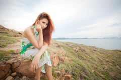 Woman sitting on a cliff Royalty Free Stock Photos