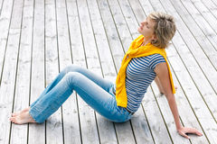 Woman sitting with closed eyes on wooden floor Royalty Free Stock Image