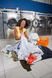 Woman Sitting With Clothes On Floor In Laundry Royalty Free Stock Photo