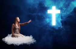 Woman sitting on a cloud looking at a cross Stock Image