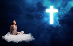 Woman sitting on a cloud looking at a cross Stock Photography