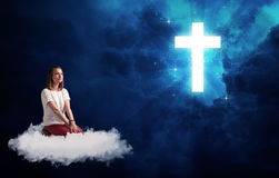 Woman sitting on a cloud looking at a cross Royalty Free Stock Photos