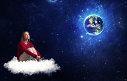 Woman sitting on cloud looking at planet earth Royalty Free Stock Image