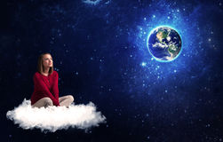 Woman sitting on cloud looking at planet earth Royalty Free Stock Photography