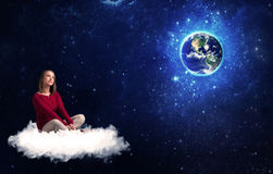 Woman sitting on cloud looking at planet earth Stock Image
