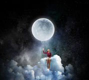 Woman sitting on cloud . Mixed media Royalty Free Stock Photography