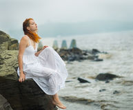 Woman sitting on the coast on beach. Redhead woman sitting on the coast on beach and looks into the distance at sea. Selective soft focus Royalty Free Stock Photo