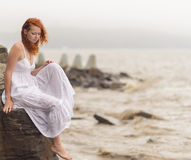 Woman sitting on the coast on beach. Stock Photo
