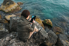 Woman sitting on coast with digital tablet Royalty Free Stock Images