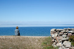Woman sitting by the coast looking at clear blue sky and water Royalty Free Stock Photography