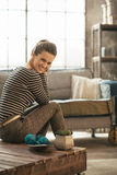 Woman sitting on coffee table in loft apartment Royalty Free Stock Image