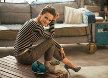 Woman sitting on coffee table in loft apartment Royalty Free Stock Images