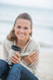 Woman sitting on cold beach with cup of beverage Stock Image