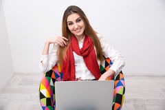 Woman sitting on the colourful chair with laptop Royalty Free Stock Photos