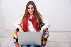 Woman sitting on the colourful chair with laptop Royalty Free Stock Photography